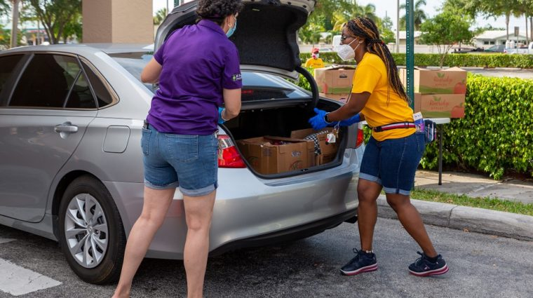 Women loading food into a car
